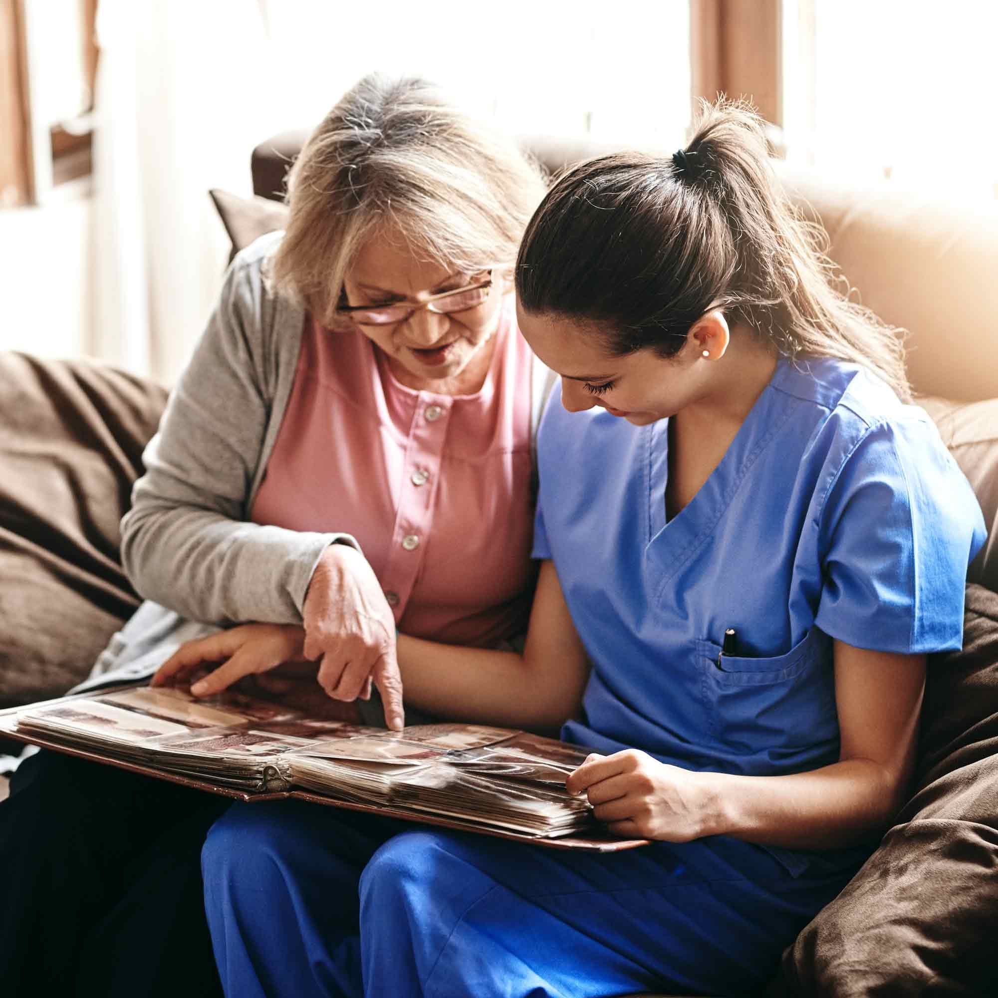 Memory Care Patient and Caretaker Looking at Pictures - The Pinnacle of Southaven